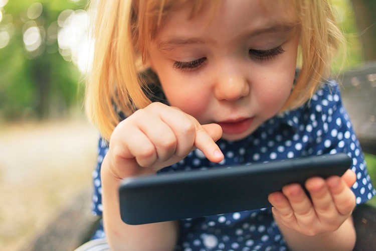 a young girl looking at a tablet