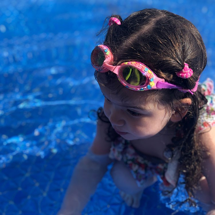 a little girl wearing goggles and a swimsuit in a pool