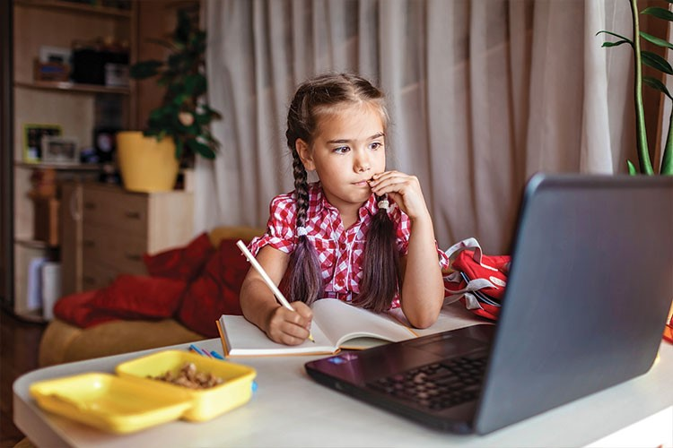 Suri Cruise sitting at a table with a laptop and a plate of food