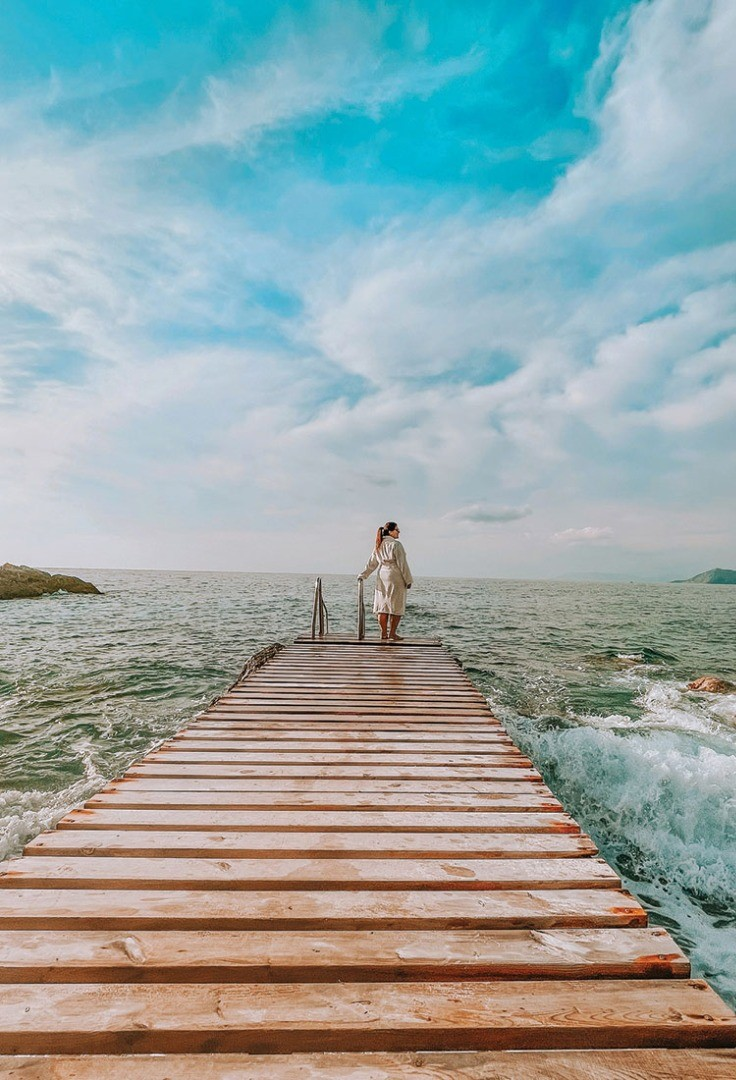 a man and woman walking on a wooden dock over water