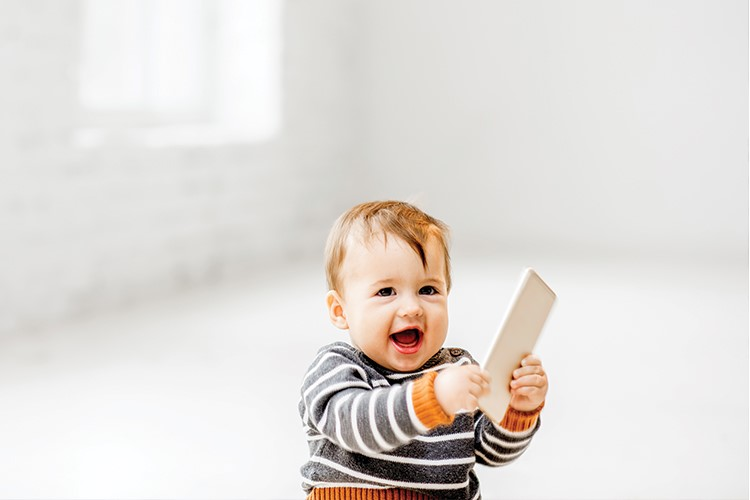 a baby holding a phone