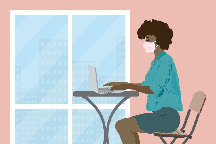 a woman wearing a mask and sitting at a desk with a computer