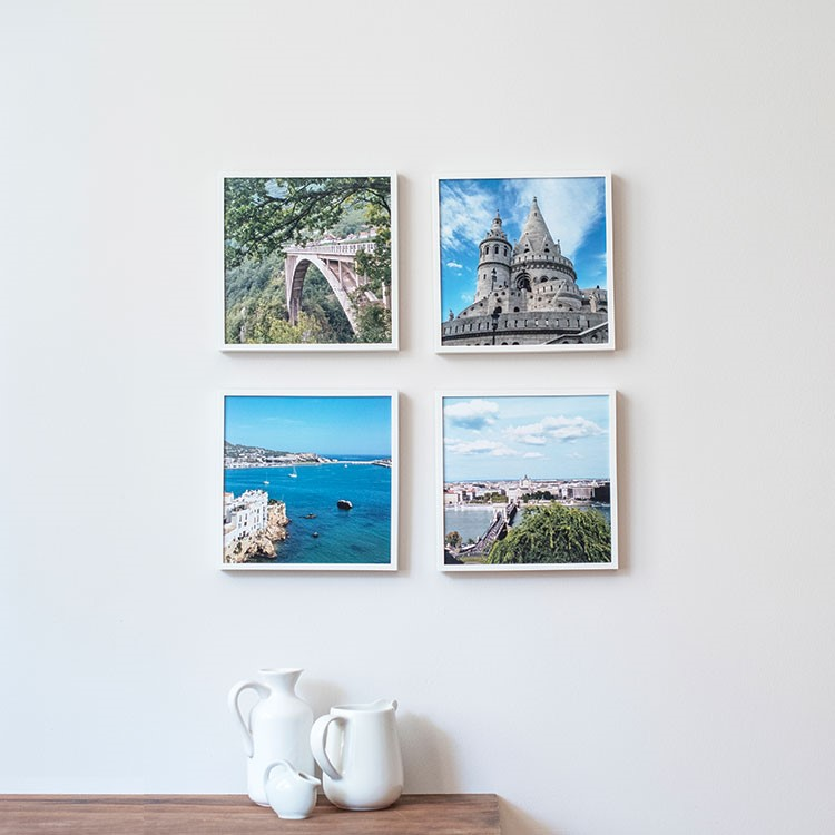 a white mug and a white mug on a table with a white wall with pictures of a city