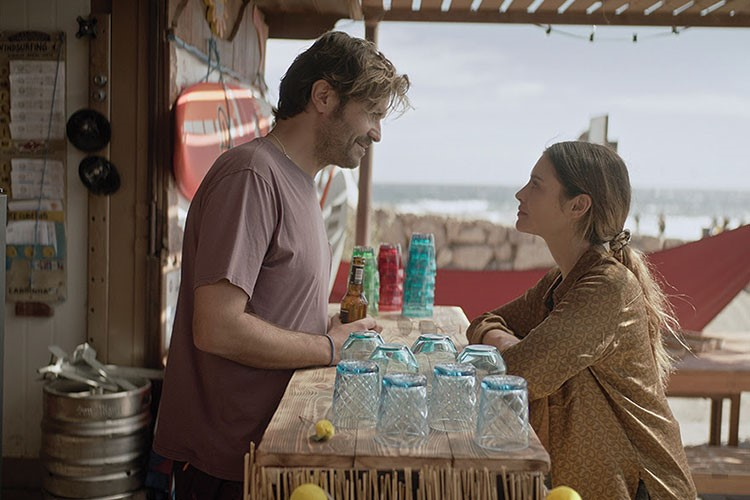 a man and a woman standing next to a table with bottles of liquid