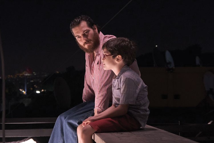 a man and woman sitting on a bench at night
