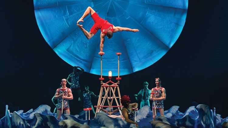 a person doing a handstand on a stage with a group of people