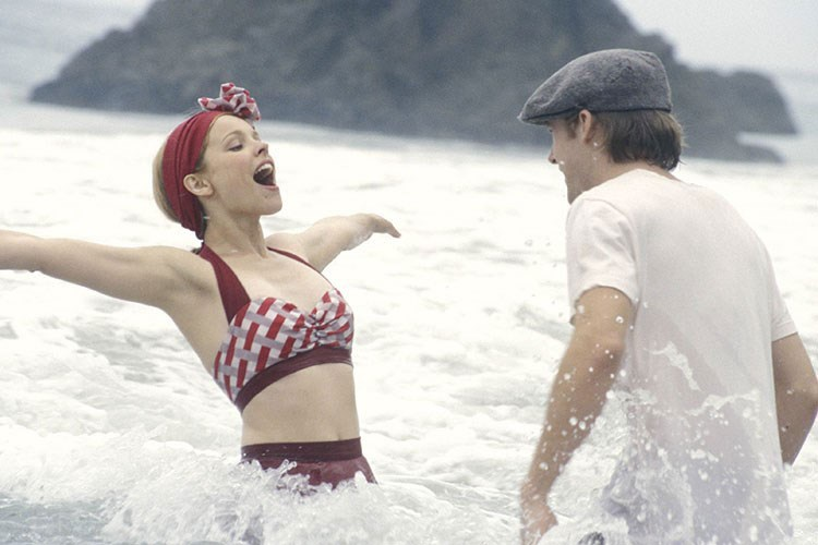 a woman in a bathing suit and a man in a white shirt in the water