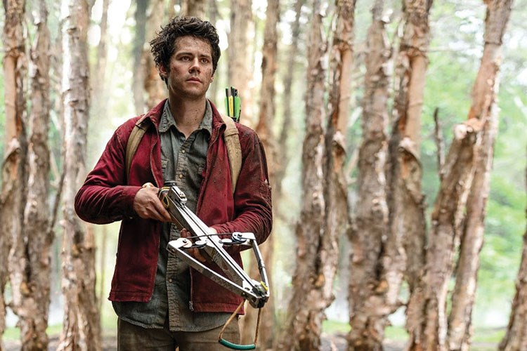 Dylan O'Brien holding a chainsaw in the woods