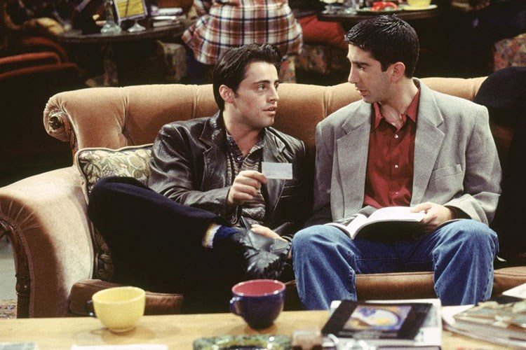 Matt LeBlanc et al. sitting on a couch looking at a book