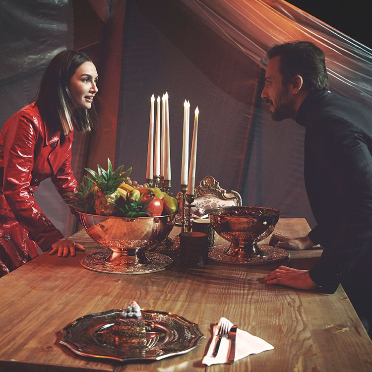 a man and woman sitting at a table with food and candles
