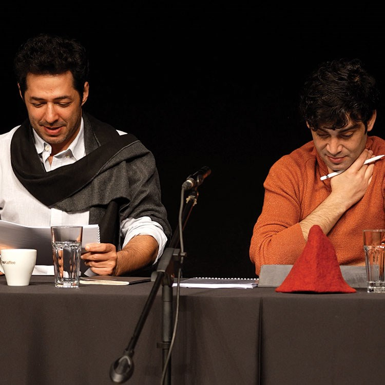 Mert Firat et al. sitting at a table with a microphone