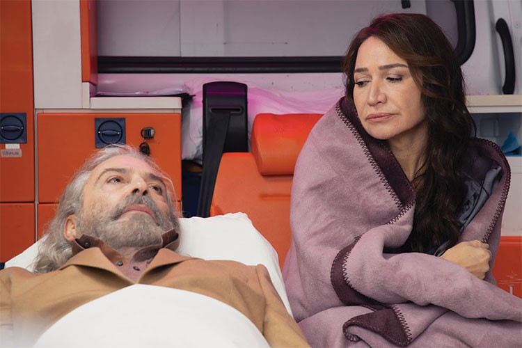 Demet Akbag sitting next to a man in a hospital bed