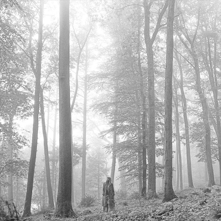a man and woman walking through a forest