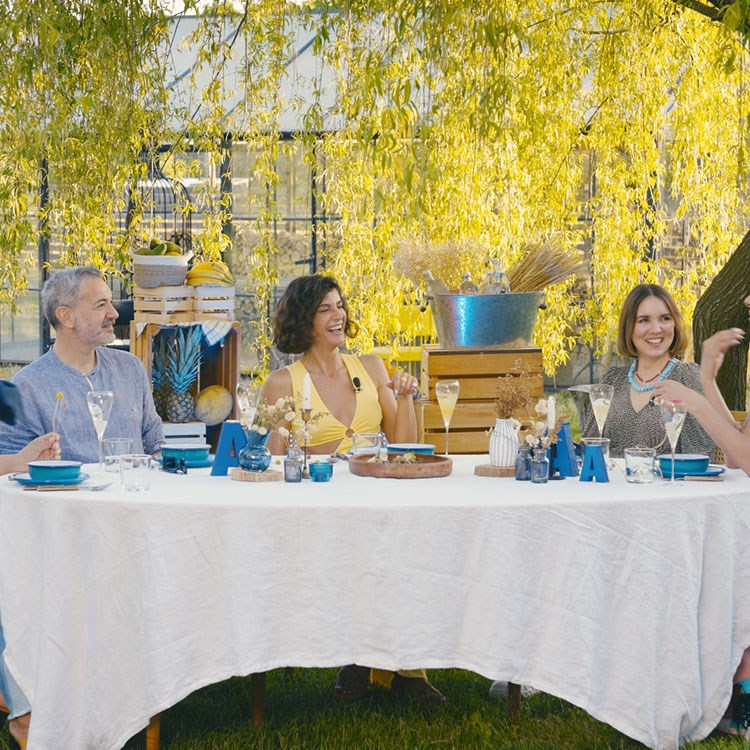 a group of people sitting at a table with food and drinks