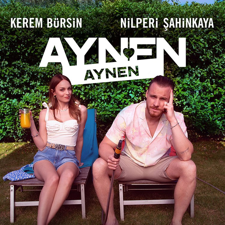 Kerem Bursin and woman sitting on a bench with drinks