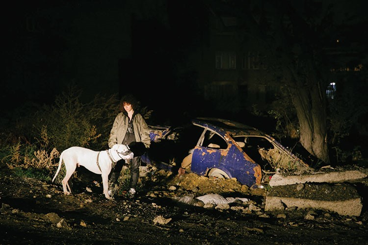 a person and a dog sitting on a pile of debris