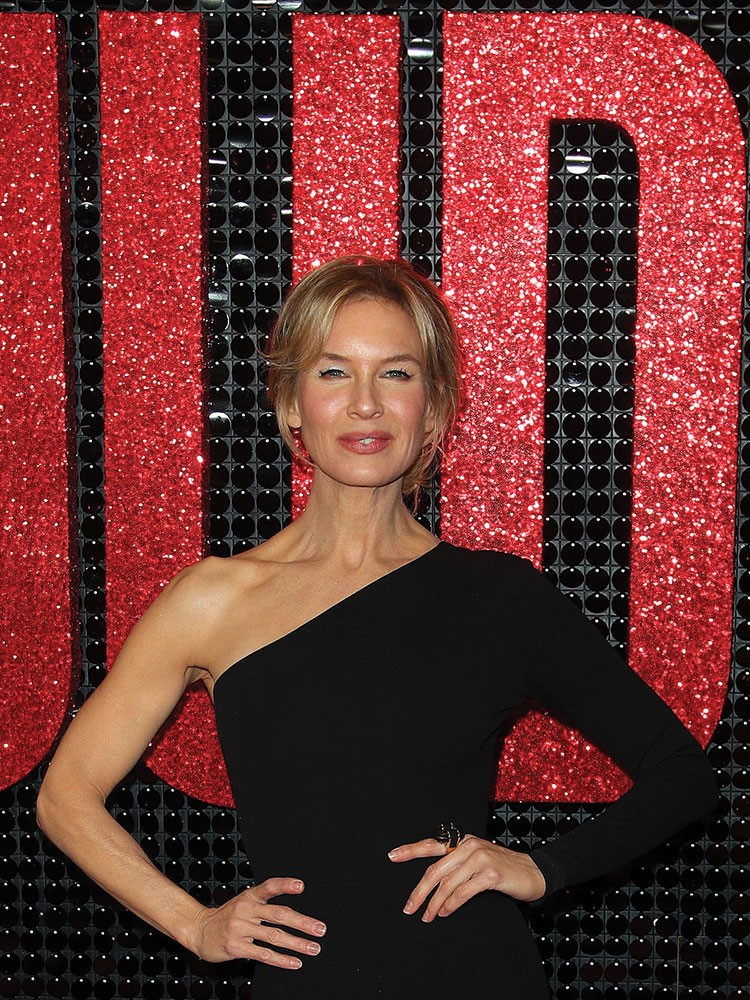 Renee Zellweger posing in front of a red curtain