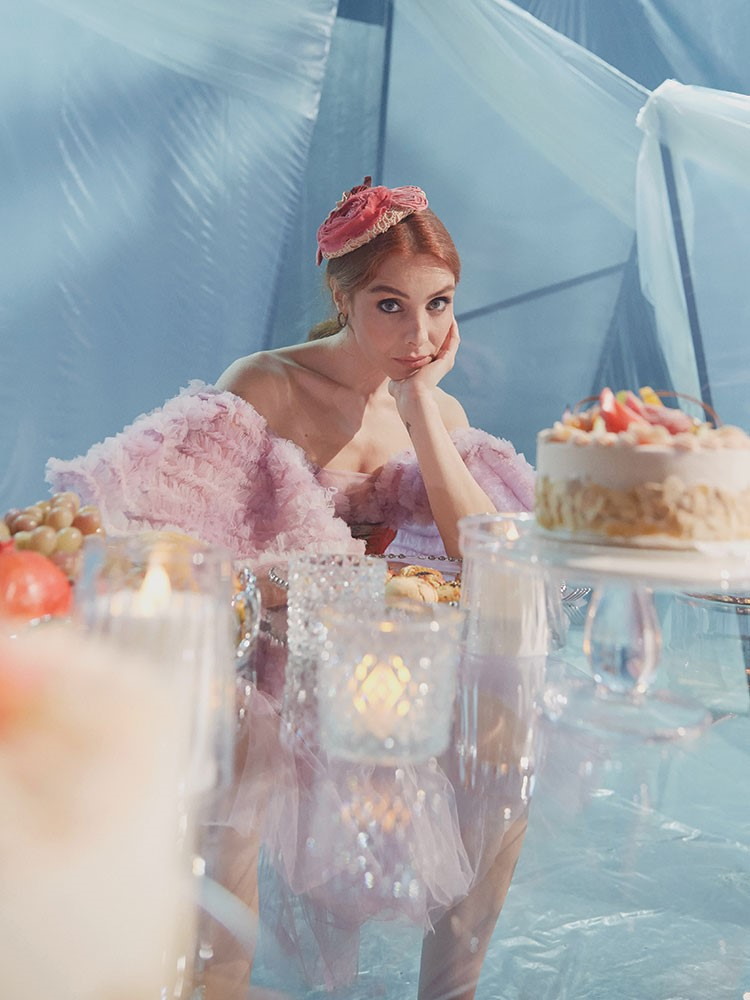 a person in a pink dress in front of a cake