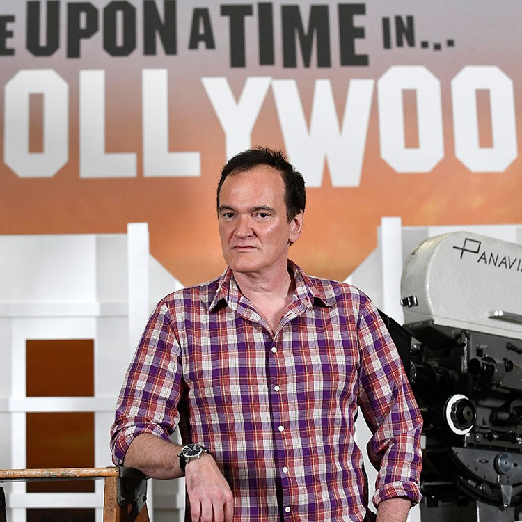 Quentin Tarantino standing in front of a sign