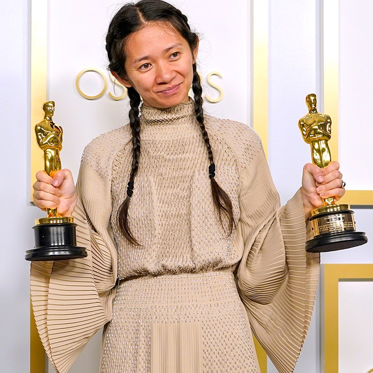 Chloé Zhao holding trophies