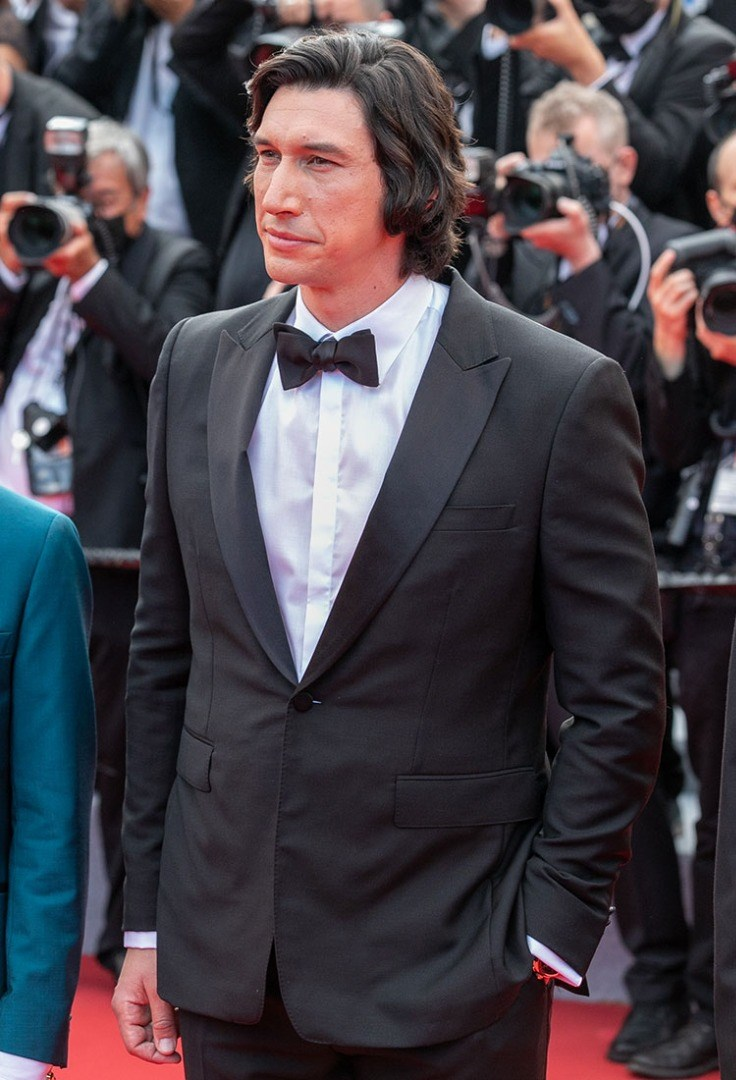 Adam Driver in a suit and bow tie walking on a red carpet