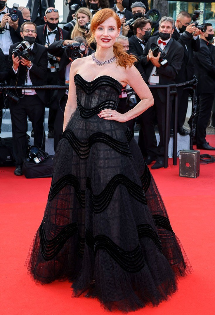 Jessica Chastain in a dress posing for a picture with a crowd of people behind the