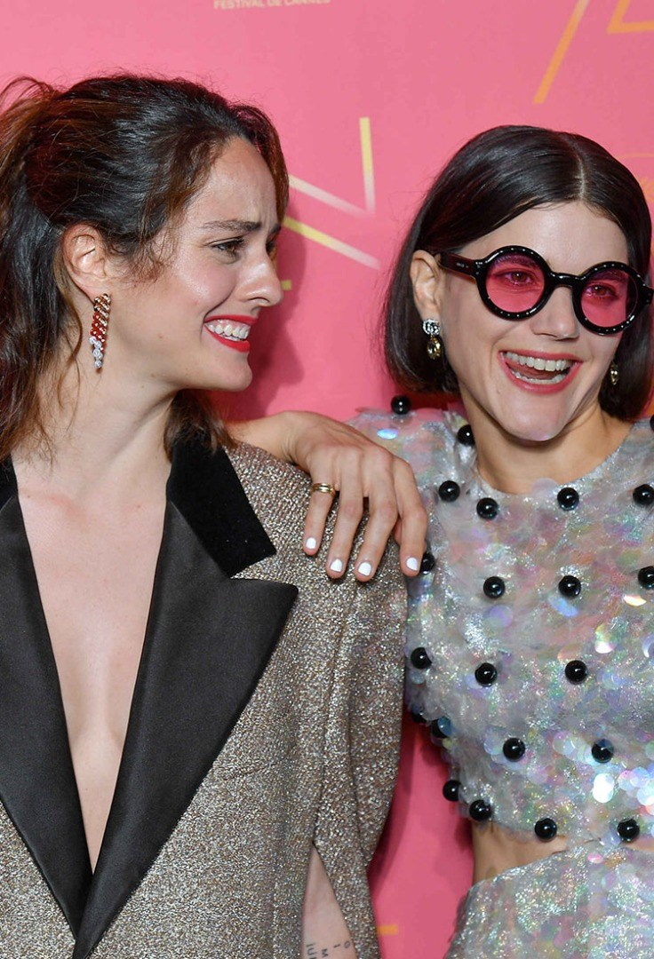 Soko with her hand on another woman's shoulder