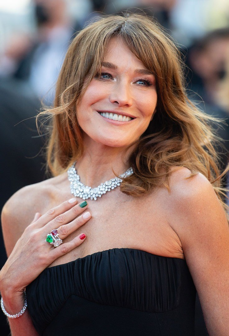 Carla Bruni smiling with her hands together