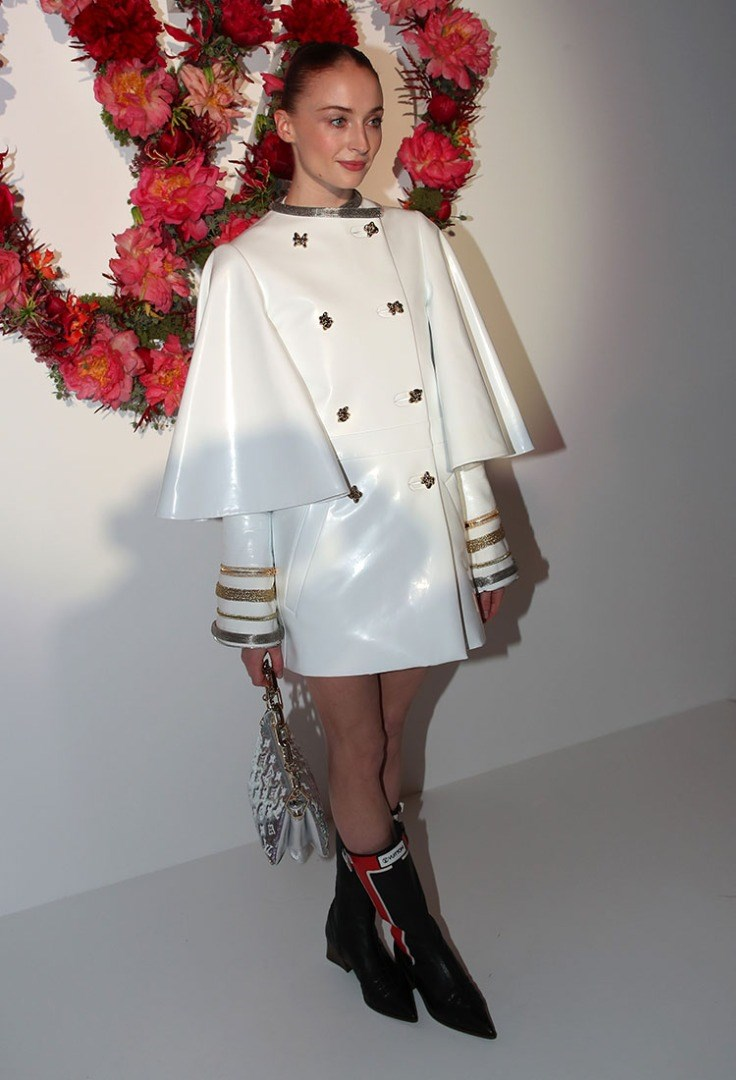 Sophie Turner wearing a white coat and black boots with a red flower on her head
