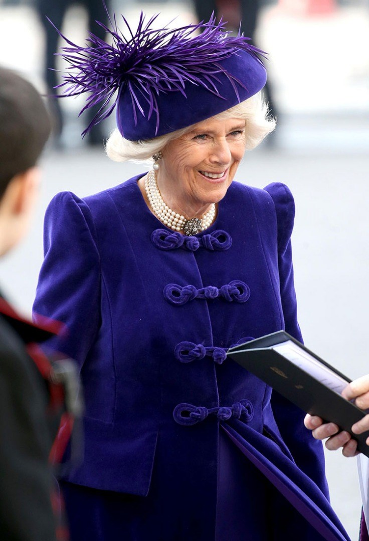 Camilla, Duchess of Cornwall in a purple dress holding a tablet