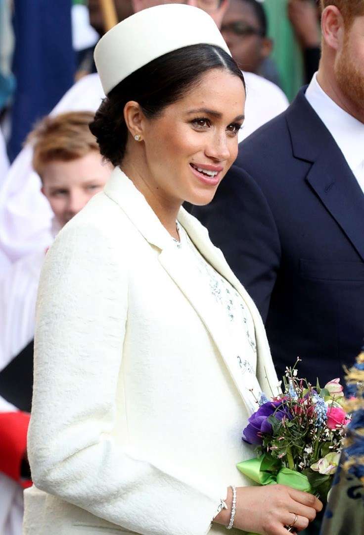 Meghan Markle in a white dress holding flowers