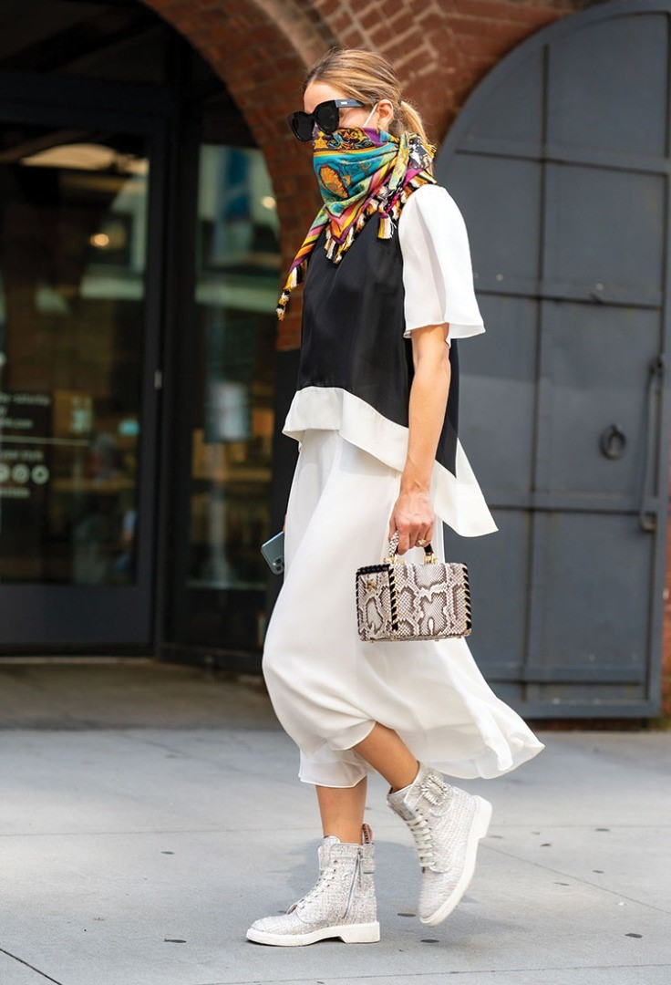 a person wearing a scarf and a skirt and a purse
