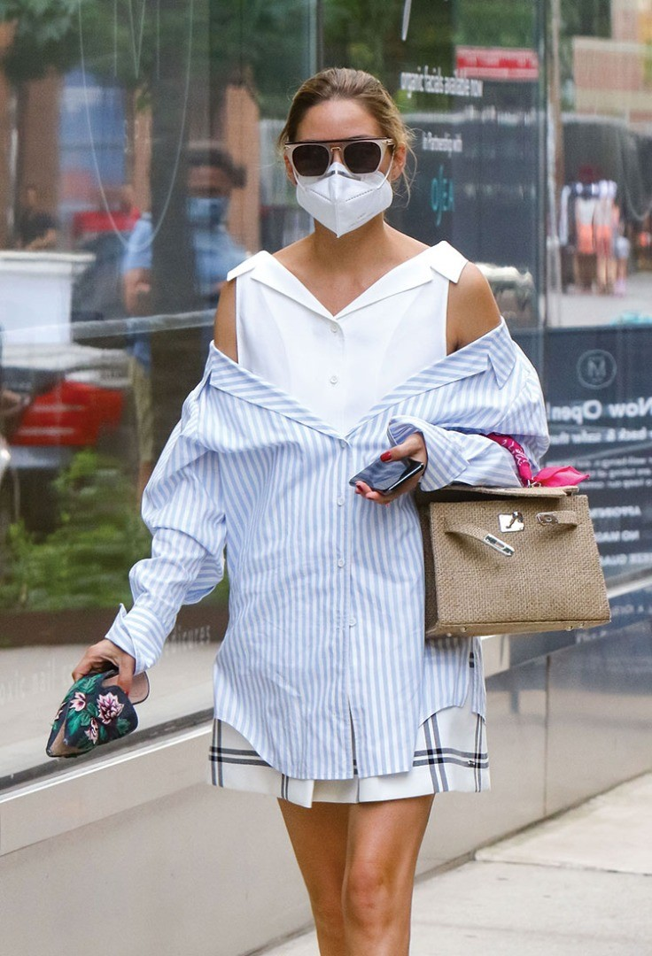 a person wearing a white shirt and sunglasses holding a purse