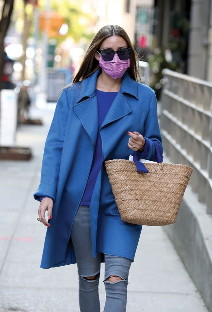 a woman wearing a blue coat and sunglasses holding a basket