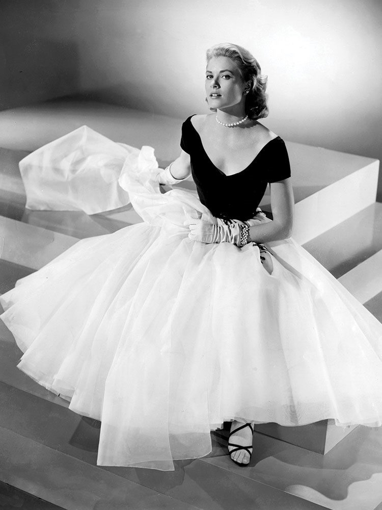 Grace Kelly in a dress sitting on a bed