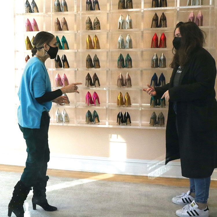 a man and woman looking at a display of shoes