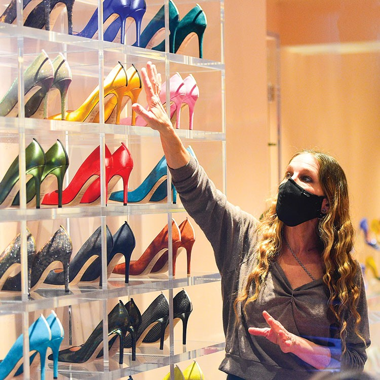 a woman posing in front of a display of shoes