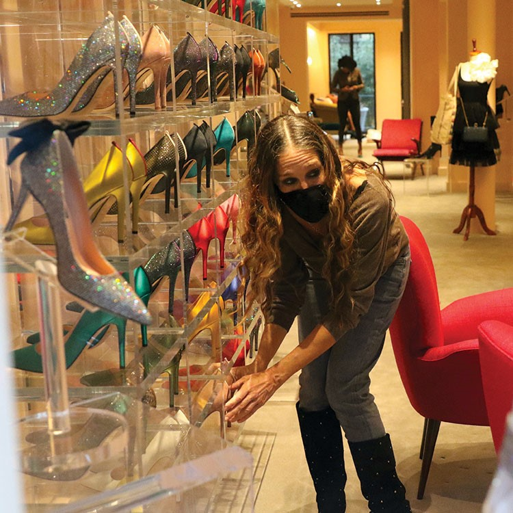 a woman posing in front of a glass display of a dinosaur