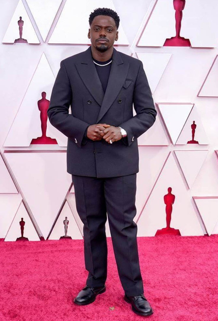 Daniel Kaluuya standing in front of a red wall