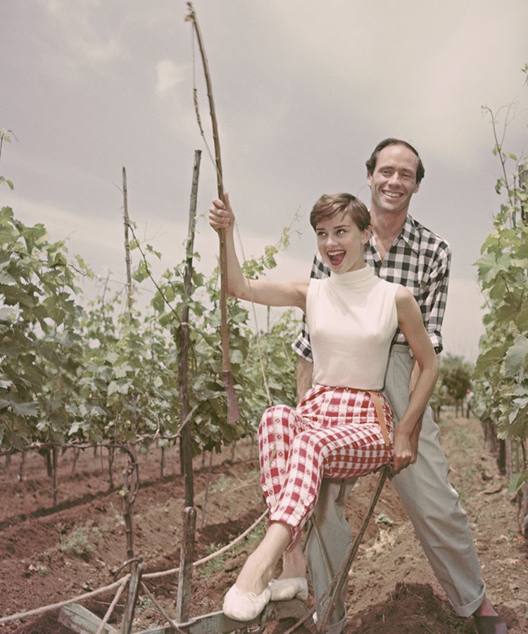 Mel Ferrer and woman standing in a field of plants