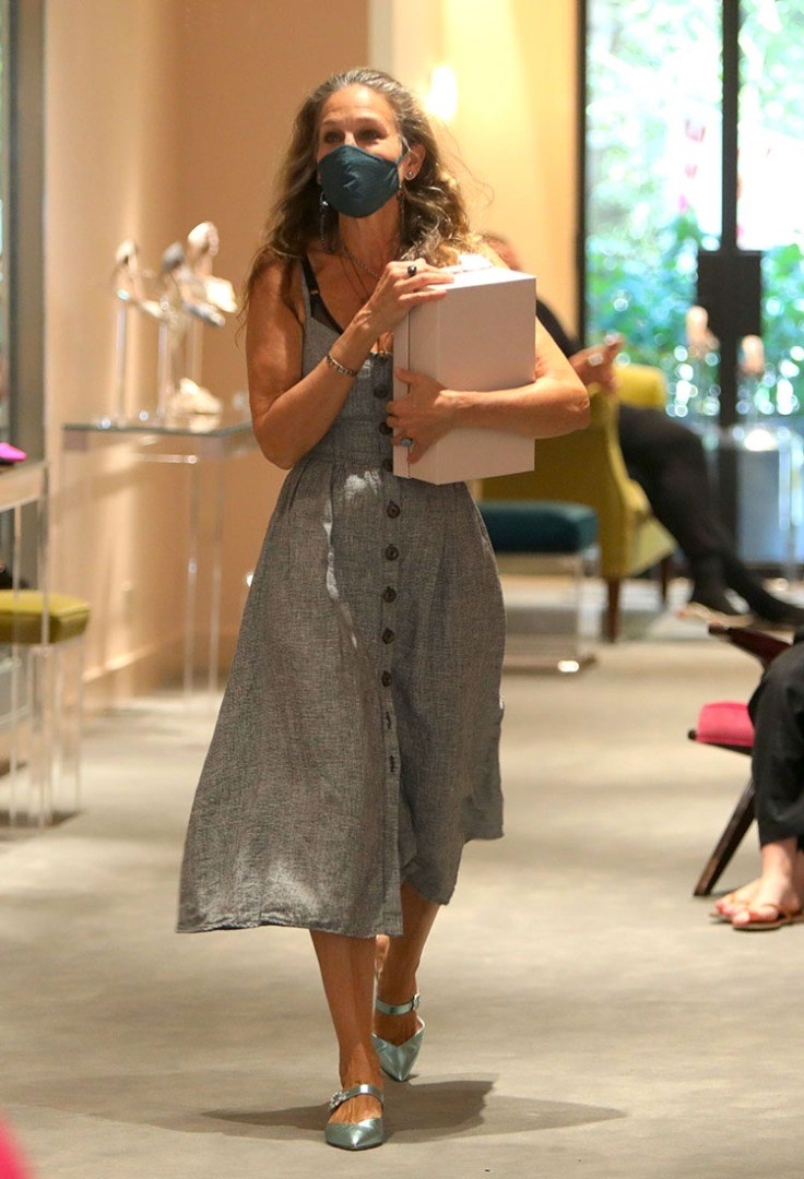 a woman wearing a dress and holding a piece of paper