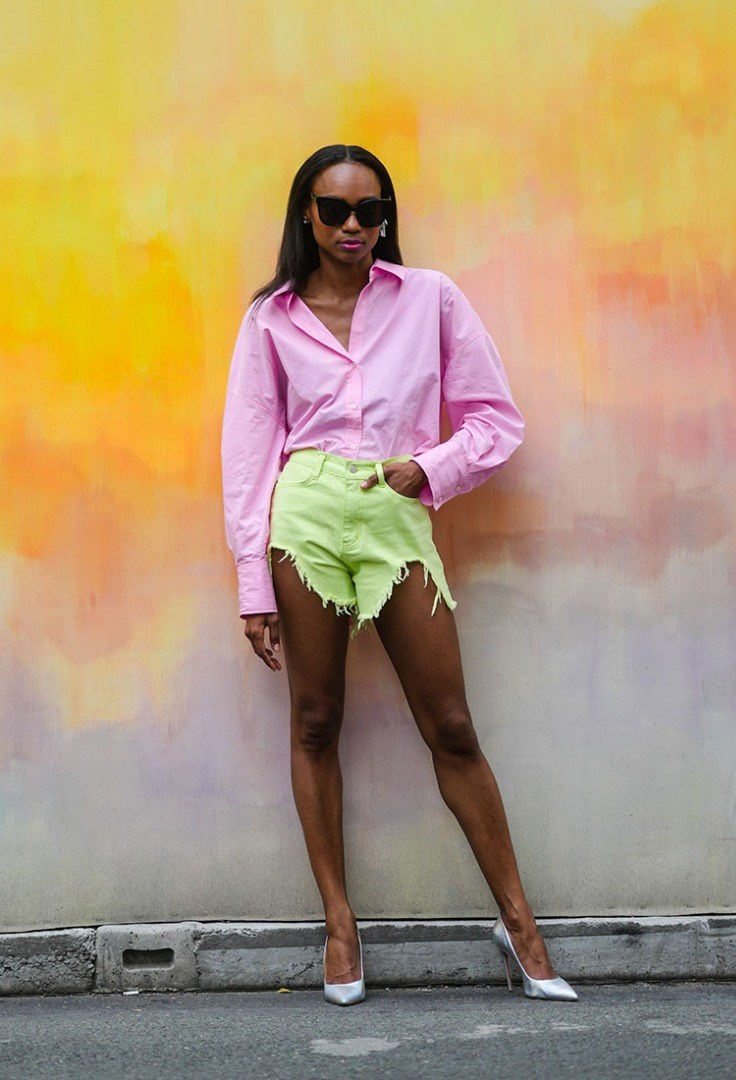 a woman in a pink jacket and sunglasses standing in front of a yellow wall