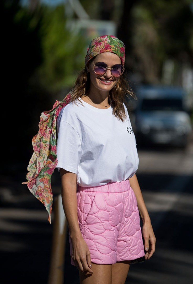 a woman wearing a pink and white shirt and sunglasses