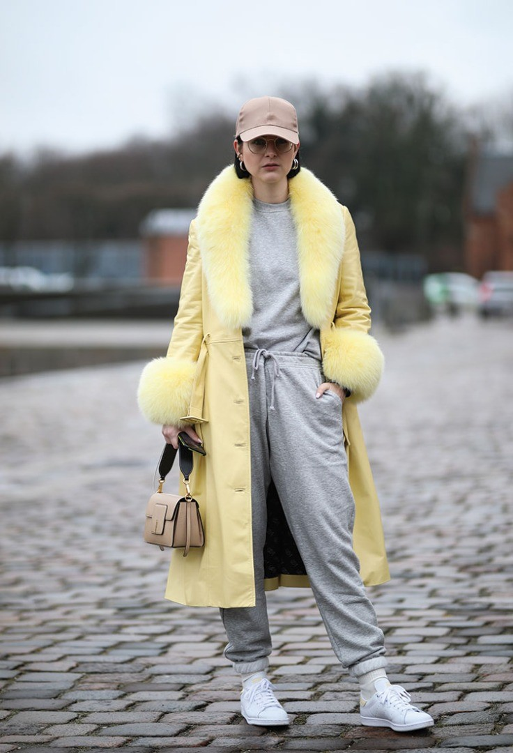 a person wearing a yellow coat and sunglasses