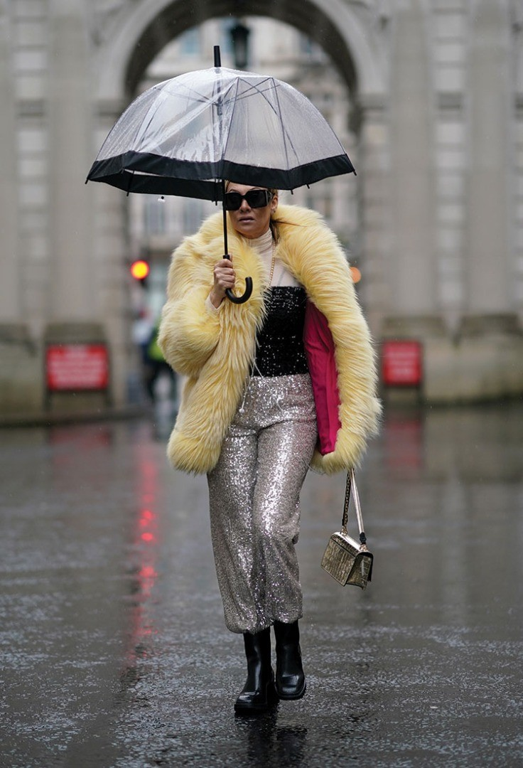 a woman walking in the rain with an umbrella