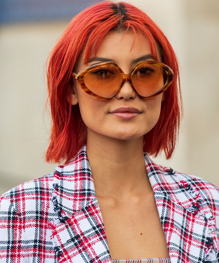 a woman with red hair wearing sunglasses