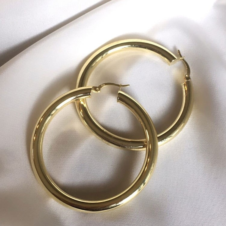 a gold ring on a white surface