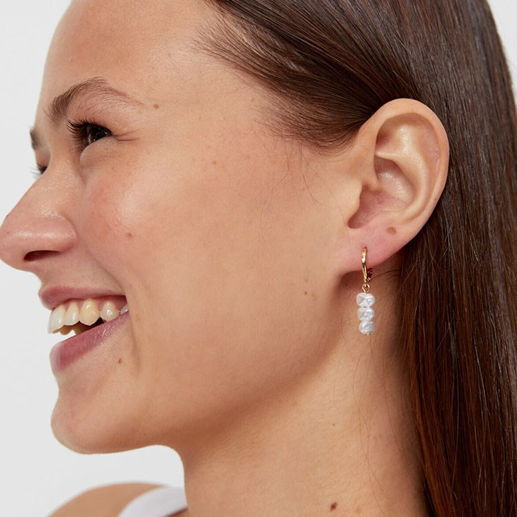 a woman with earrings smiling