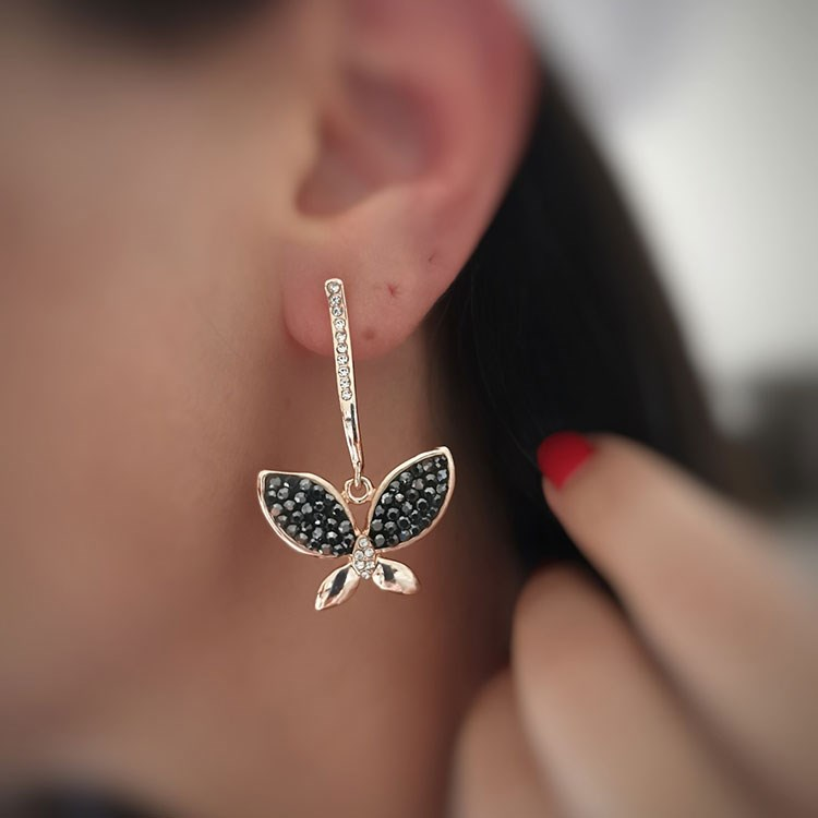 a woman's ear with a necklace and a diamond pendant