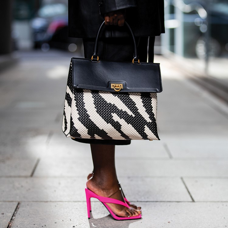 a person wearing a black and white dress and pink heels